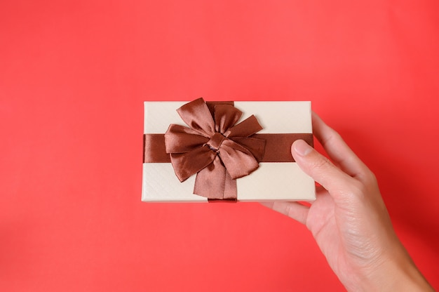 Trzyma dawać prezenta pudełku na czerwonym tle.