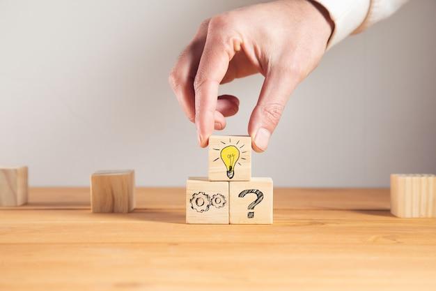 Trzyma drewnianą kostkę z żarówką i pomysłem