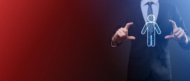 Trzyma ikonę osoby człowieka na ciemnym tle. hr człowieka, peopletechnology process system business