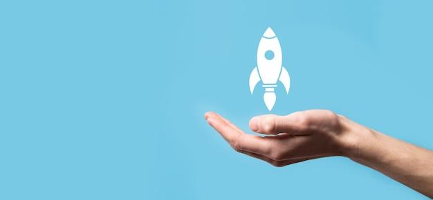 Trzyma ikonę rakiety, która startuje, launch.rocket startuje i wylatuje, rozpoczęcie działalności