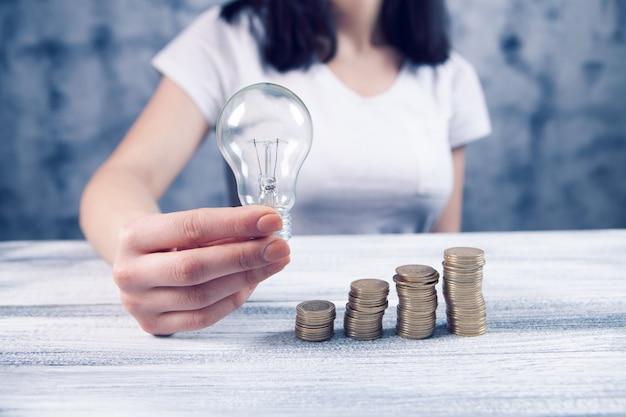 Trzyma lampkę obok monet na schemacie