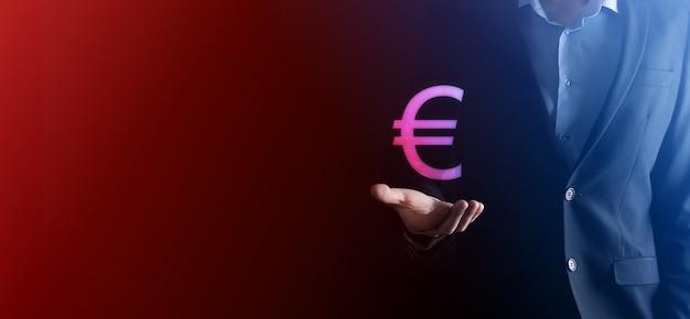 Trzyma pieniądze monety ikony eur lub euro na ciemnym tle tonu... rosnąca koncepcja pieniędzy dla biznesu