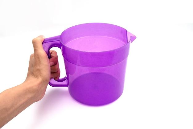 Trzyma plastikowy czajnik na białym tle