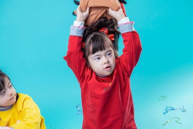 Trzyma różowy plusz. uważne małe dziecko w czerwonej bluzie z kapturem wznoszące zabawkę pod głowę