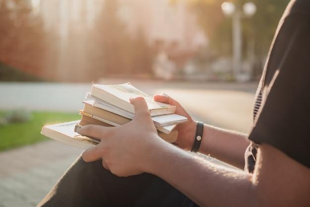 Trzyma stos książek studenckich poza szkołą. student pierwszego roku czeka na rozpoczęcie zajęć