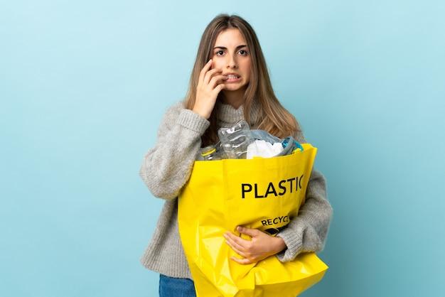 Trzyma torbę pełną plastikowych butelek, aby poddać je recyklingowi na odosobnionym niebieskim, zdenerwowanym i przestraszonym