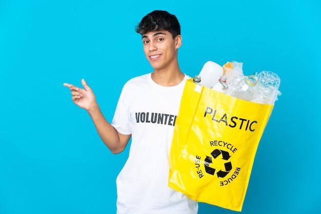 Trzyma torbę pełną plastikowych butelek do recyklingu na niebieskim tle, wskazując palcem w bok