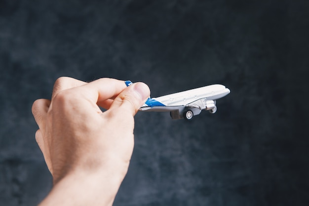 Trzyma w ręku mały samolot