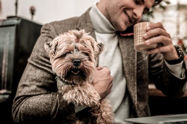 Trzyma zabawnego psa. mężczyzna trzyma małego teriera podczas picia kawy