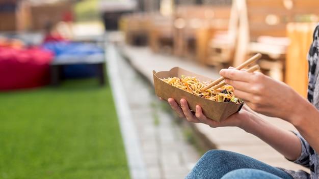 Trzymać chińskiego jedzenie z zamazanym tłem