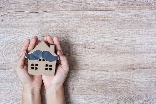 Trzymać domu modela z wąsem na drewnianym tle dla ojców.