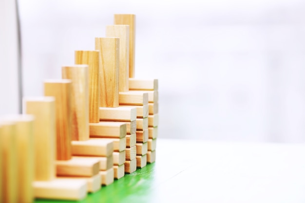 Trzymać drewniany blok stojący na ułożonych kwadratowych blokach drewnianych, abstrakcyjne tło w koncepcji wygranej, sukcesu, wyzwania, krok do najwyższej pozycji.