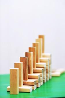 Trzymać drewniany blok stojący na ułożonych kwadratowych drewnianych blokach abstrakcyjne tło