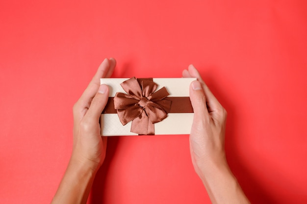 Trzymać prezenta pudełko na czerwonym tle.