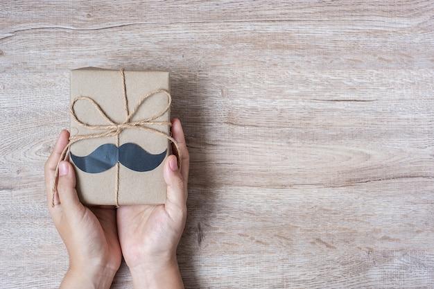 Trzymać prezenta pudełko z wąsem na drewnianym tle
