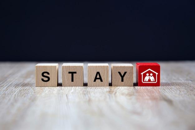 Trzymaj domowe ikony tekstowe na drewnianym bloku zabawek. pojęcia dotyczące zdrowia i profilaktyki medycznej koronawirusa lub zakażenia covid-19.