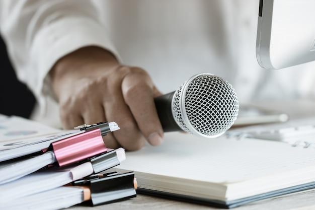 Trzymaj nauczyciela / głośnika mikrofon z dokumentem papierowym na seminarium do mówienia lub wykład na uniwersytecie w klasie z pulpitem komputera na biurku. konferencja mowy w szkole. vintage ton