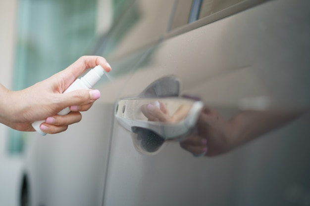 Trzymaj ręką butelkę rozpyloną alkoholem dezynfekującą klamkę drzwi samochodu, w celu ochrony przed wirusem koronowym lub ochroną covid-19.