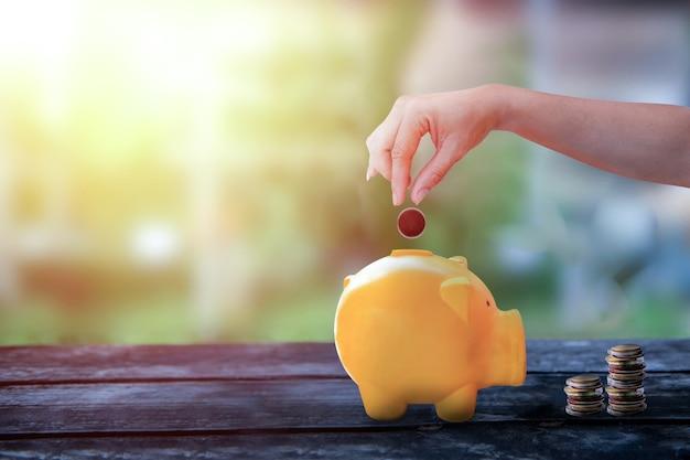 Trzymaj rękę i upuszczając monetę w piggy żółty skarbonka, skarbonka na starym drewnianym stole z niewyraźnym tłem, koncepcja bezpiecznych pieniędzy