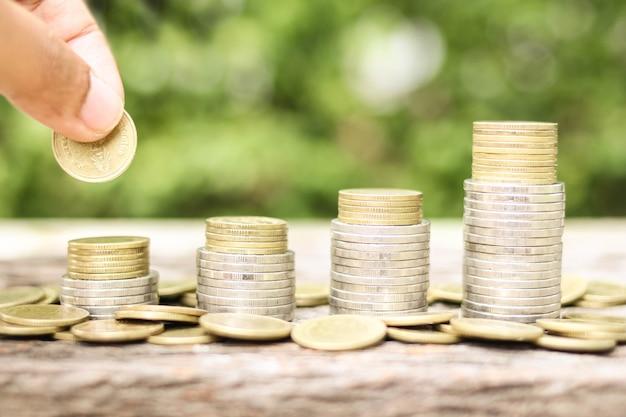 Trzymaj rękę inwestora i upuść złotą monetę z oszczędności pieniędzy na rozmycie tła fotografii inwestycje biznesowe i koncepcja oszczędności pieniędzy