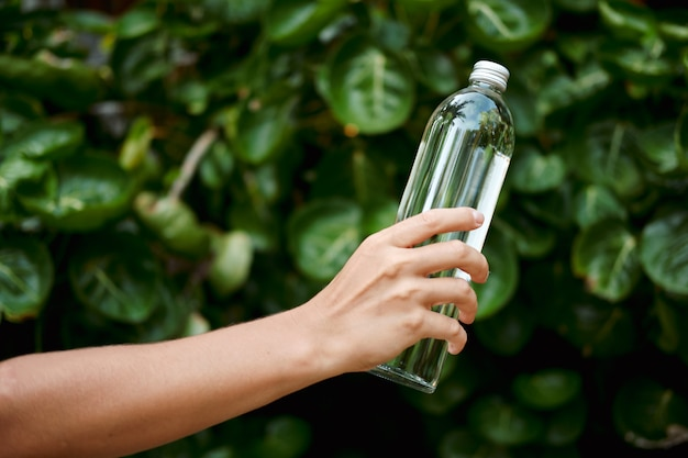 Trzymaj rękę woda przezroczysta szklana butelka wielokrotnego użytku