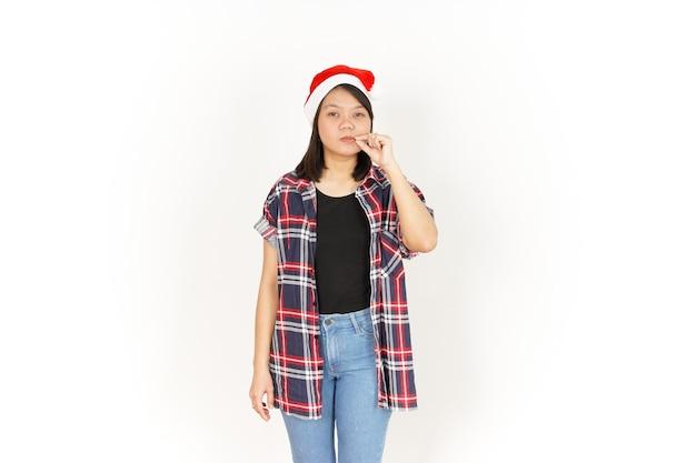 Trzymaj sekretną wargę pięknej azjatyckiej kobiety ubranej w czerwoną koszulę w kratę i santa hat