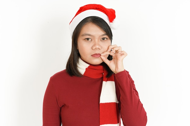 Trzymaj sekretną wargę pięknej azjatyckiej kobiety w czerwonym golfie i czapce świętego mikołaja na białym tle