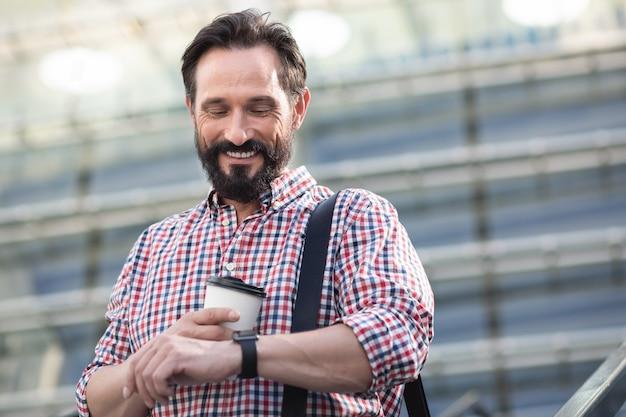 Trzymaj się czasu. radosny przystojny mężczyzna sprawdzanie czasu podczas picia kawy na świeżym powietrzu