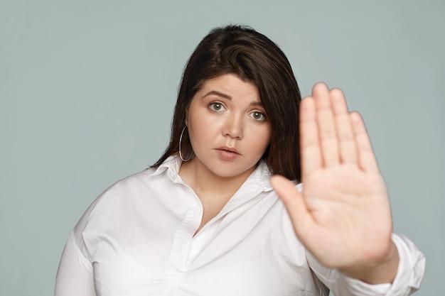 Trzymaj się ode mnie z daleka. poważna niezadowolona młoda brunetka pulchna sekretarka w oficjalnym stroju wpatrzona, wyciągająca rękę, wykonująca gest stopu dłonią, wyrażająca odmowę lub odrzucenie