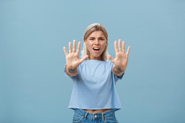 Trzymaj się tam. portret intensywnie niezadowolonej i zirytowanej, atrakcyjnej młodej kobiety w niebieskiej koszulce wyciągającej ręce w kierunku zatrzymania lub braku gestu marszcząc brwi i robiąc zirytowany wyraz twarzy
