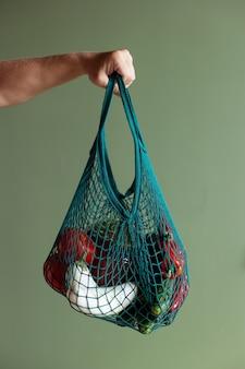 Trzymaj się za ręce ustaw różne warzywa z woreczkiem sznurkowym na zielonym tle. dostawa zdrowej żywności