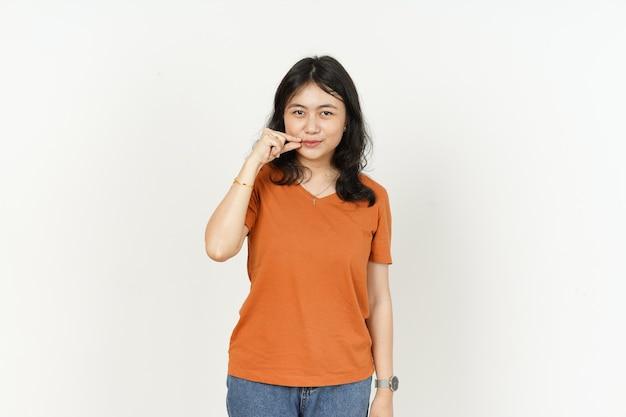 Trzymaj tajemnicę zamkniętą wargę pięknej azjatyckiej kobiety noszącej pomarańczową koszulkę na białym tle