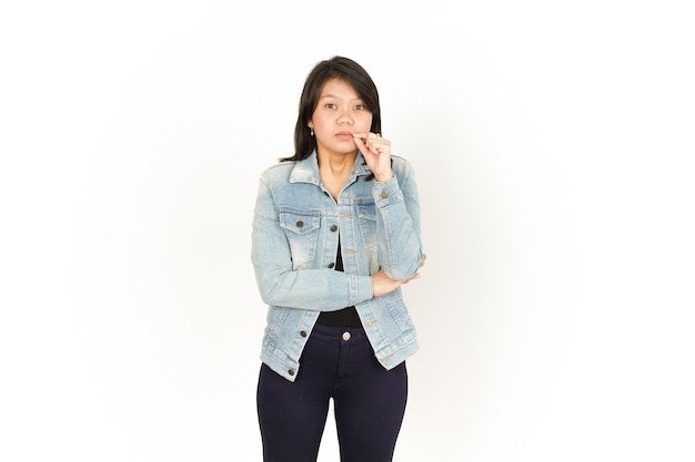 Trzymaj tajemnicę zamkniętą wargę pięknej azjatyckiej kobiety ubrana w dżinsową kurtkę i czarną koszulę na białym tle