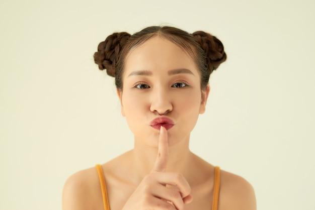 Trzymaj w tajemnicy! portret figlarnie pozytywna azjatycka nastolatka z fryzurą bułki pokazujący ciszę gest na jasnym tle.