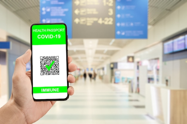 Trzymaj za rękę telefon podróżny z paszportem zdrowotnym potwierdzającym szczepienia karta zdrowia na lotnisku została zaszczepiona na koronawirusa covid19