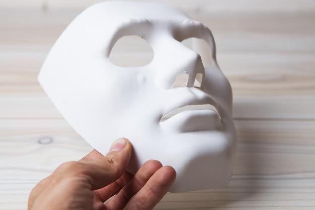 Trzymając białą anonimową maskę
