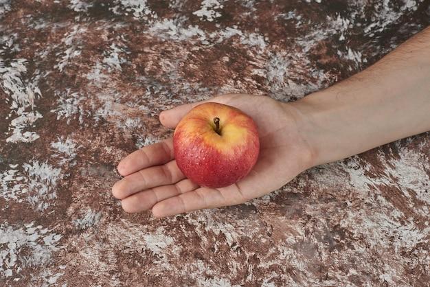 Trzymając czerwone jabłko w dłoni.