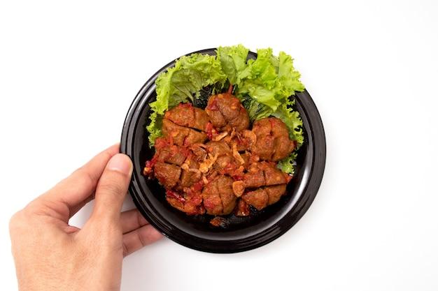 Trzymając domowe klopsiki z sosem pomidorowym i przyprawami podawane na czarnym talerzu na białym tle