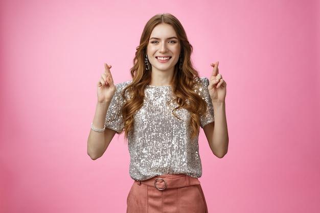 Trzymając kciuki wierna optymistyczna uśmiechnięta atrakcyjna młoda kaukaska glamour dziewczyna składa życzenia dobre l...