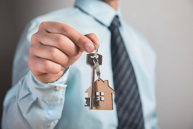 Trzymając klucze do domu na szarej ścianie