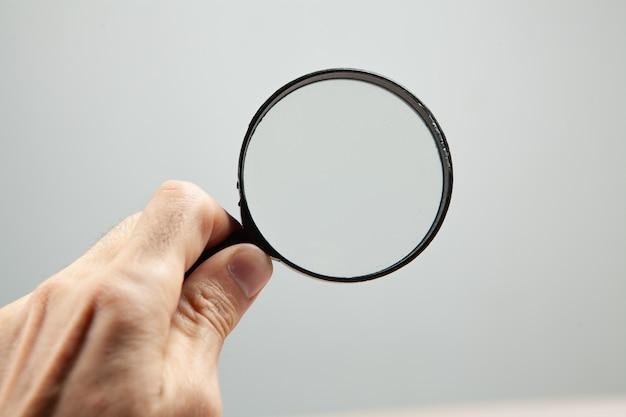 Trzymając lupę na szarym tle. koncepcja wyszukiwania