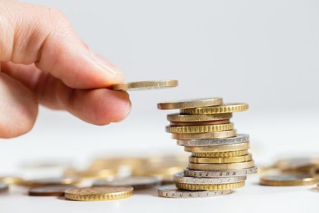 Trzymając monetę w palcach nad stosem pieniędzy z bliska.
