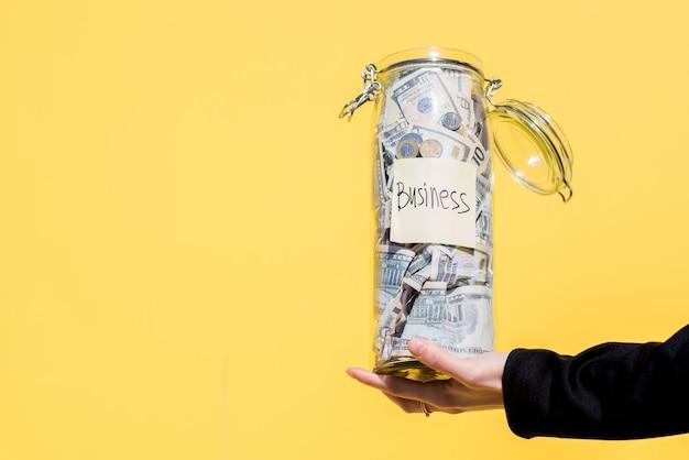 Trzymając na żółtym tle szklaną butelkę pełną oszczędności na inwestycje biznesowe