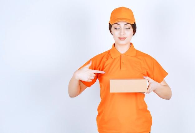 Trzymając paczkę z dostawą i wskazując ją palcem