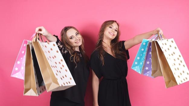 Trzymając paczki w rękach, dwie szczęśliwe dziewczyny patrzą w kamerę na różowym tle