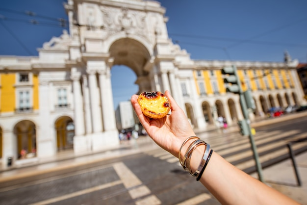 Trzymając portugalskie ciasto z tartą jajeczną o nazwie pastel de nata na zewnątrz na tle łuku triumfalnego w lizbonie