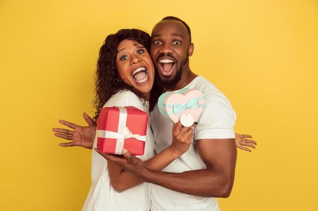 Trzymając pudełka na prezenty. obchody walentynek, szczęśliwa para afroamerykańska na białym tle na żółtym tle studio.
