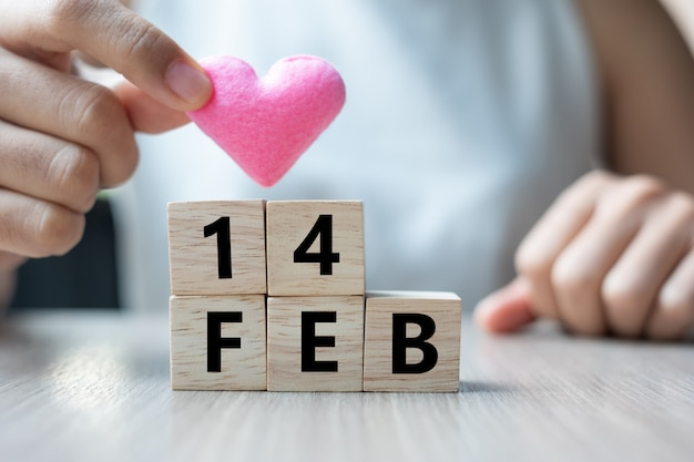 Trzymając różowy kształt serca z drewnianym sześcianem