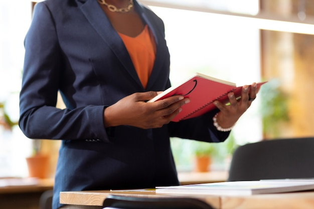 Trzymając różowy notatnik. kobieta ubrana w niebieską kurtkę, trzymająca różowy notatnik i czytająca notatki