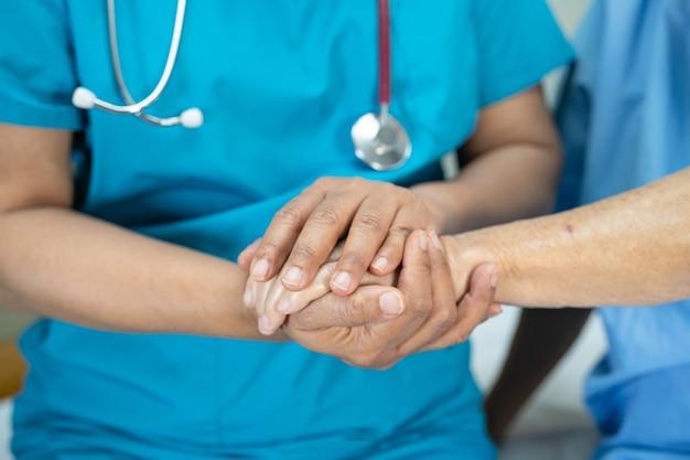 Trzymając się za ręce azjatycka starsza lub starsza kobieta starsza kobieta z miłością, opieką, zachęcaniem i empatią na oddziale szpitala pielęgniarskiego, zdrowa, silna koncepcja medyczna